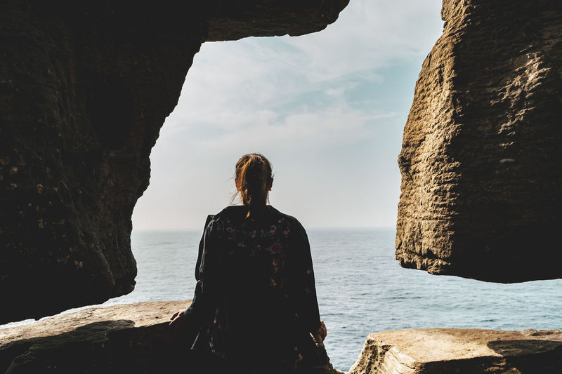 Woman looking at sea from cave against sky