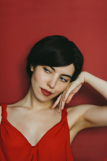 Portrait of a beautiful young woman against red background