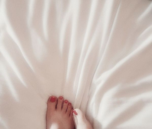 Low section of woman legs on bed