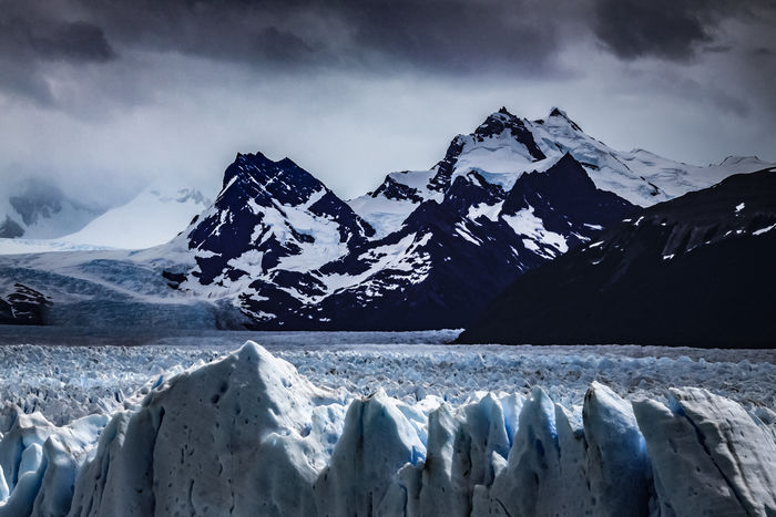 The Patagonian Andes guard the entrance to the Southern Ice Field as the Perito Moreno Glacier slowly makes its way down to the lower ground of Argentino Lake. At its end the Perito Moreno Glacier has an average thickness of 170m (558ft) with 74m (240ft) visible above the water line above the lake. With over 250 km2 (97 sq mi) of ice the glacier spans 30 km (19 mi) in length and a width of 5km at its terminus. Since 1968 rupturing ice has taken the lives of 32 people who were hit by flying ice. One of 48 glaciers that form part of the Southern Patagonian Ice Field, the high altitude field has a total area of 12,363 km2 (4,773 sq mi) of ice. Los Glaciares National Park, Santa Cruz , Argentinean Patagonia, Argentina. Love Life, Love Photography America Andes Argentina Blue Calafate Clouds Cruz El Glaciares Glacier Ice Ice Los Moreno Mountain Mountain Range Mountains Patagonia Perito Santa Sky Snow South Travel Water Perspectives On Nature
