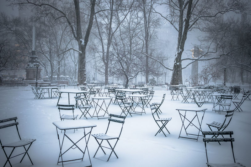 Snow covered tables and chairs in park
