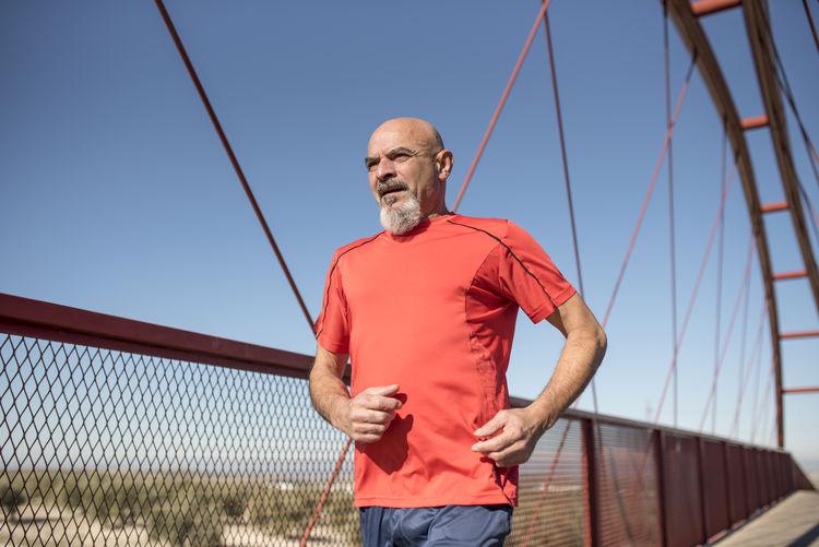 Mature man running on bridge