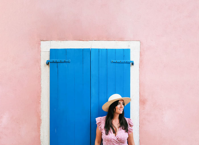 Woman in pink dress standing by blue door, window on pink wall.