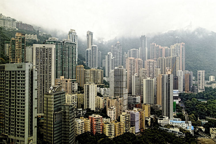 View over skyscrapers to foggy Victoria Peak, Hong Kong Architecture Building Exterior Building Story Built Structure City City Life Cityscape Crowded Development Fog Growth Modern Mountain Office Building Outdoors Sky Skyscraper Tall Tower Travel Destinations Victoria Peak, Hongkong View Weather Wide Wide Shot