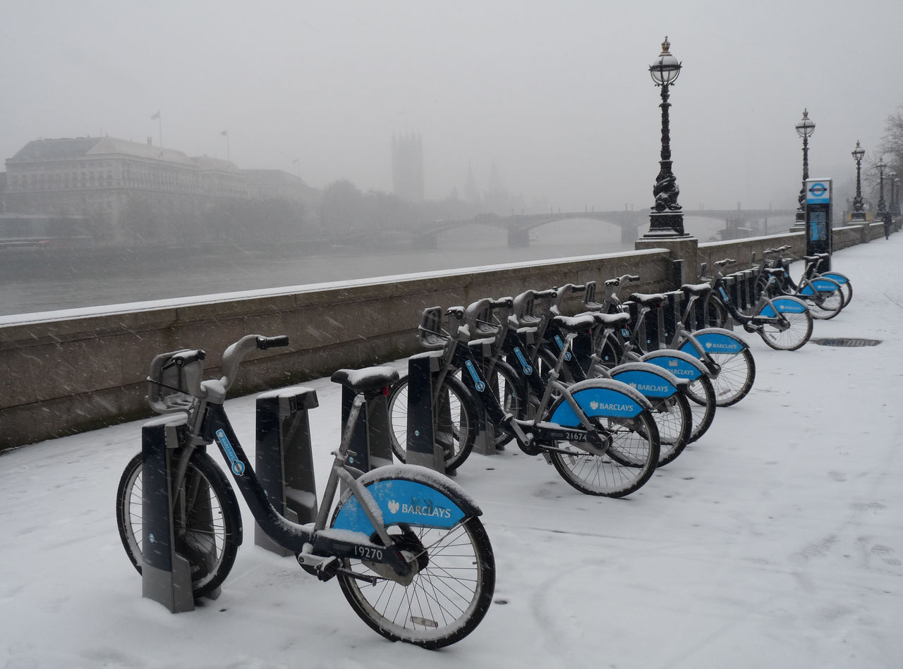 bicycle, transportation, mode of transport, stationary, bicycle rack, in a row, land vehicle, outdoors, no people, day, winter, built structure, snow, cold temperature, fog, architecture, city, nature