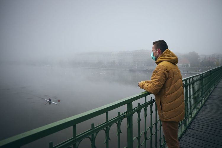 Man wearing mask standing by railing on bridge against sky during winter