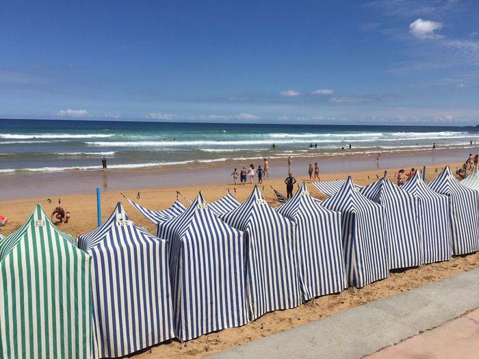 Hooded beach chairs at beach against sky