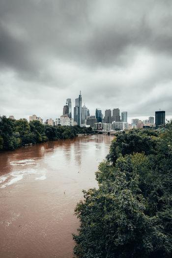 Buildings in city against cloudy sky philadelphia river