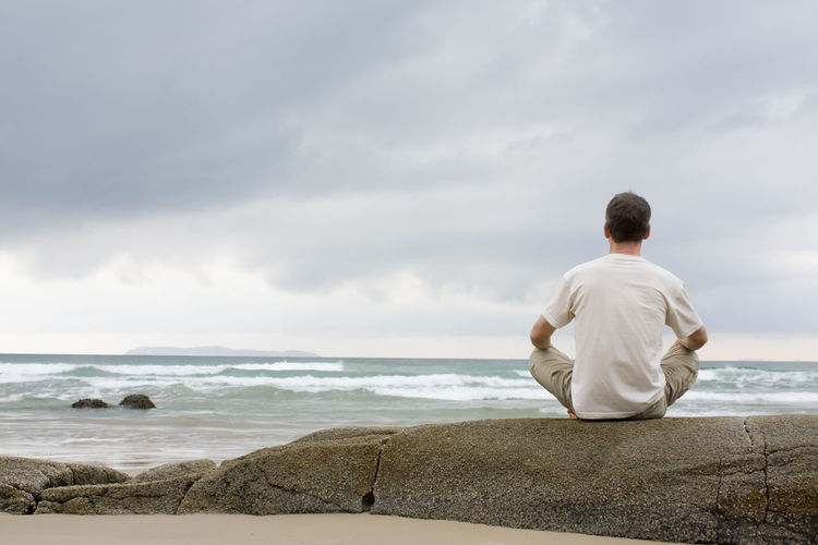 Man meditating on a rock at the sea barefoot
