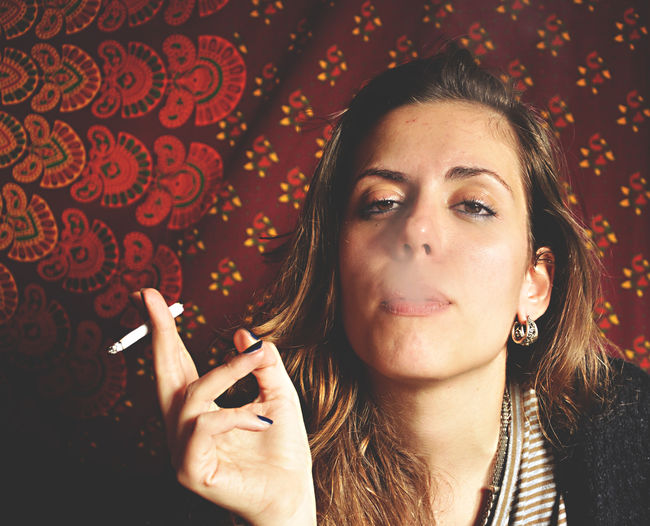 Portrait of young woman exhaling smoke