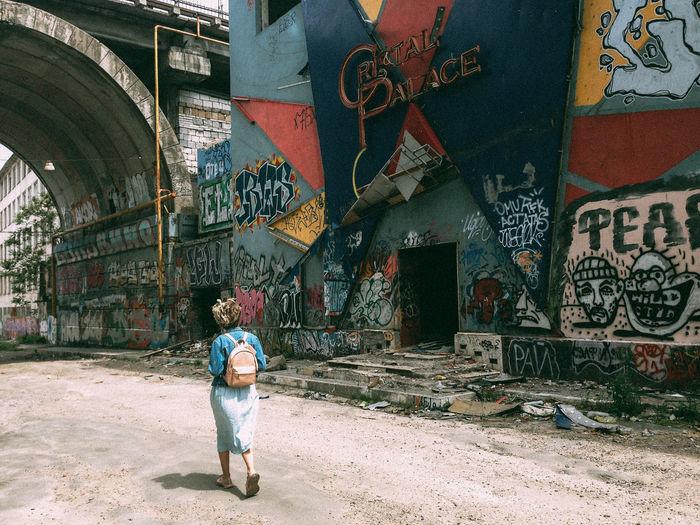 Rear view of woman walking on graffiti wall