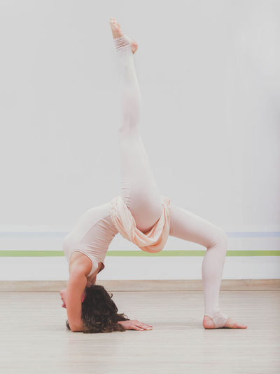 Full Length Of Young Woman Doing Yoga Against Wall