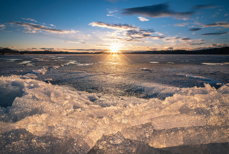 Scenic landscape with sunset and melting ice at beautiful evening in Finland Bright Finland Melting Nature Atmospheric Mood Beauty In Nature Bright Cloud - Sky Cold Temperature Crystal Ice Idyllic Landscape Melting Ice Nature No People Scenics - Nature Sky Snow Sun Sunlight Sunset Tranquil Scene Tranquility Winter