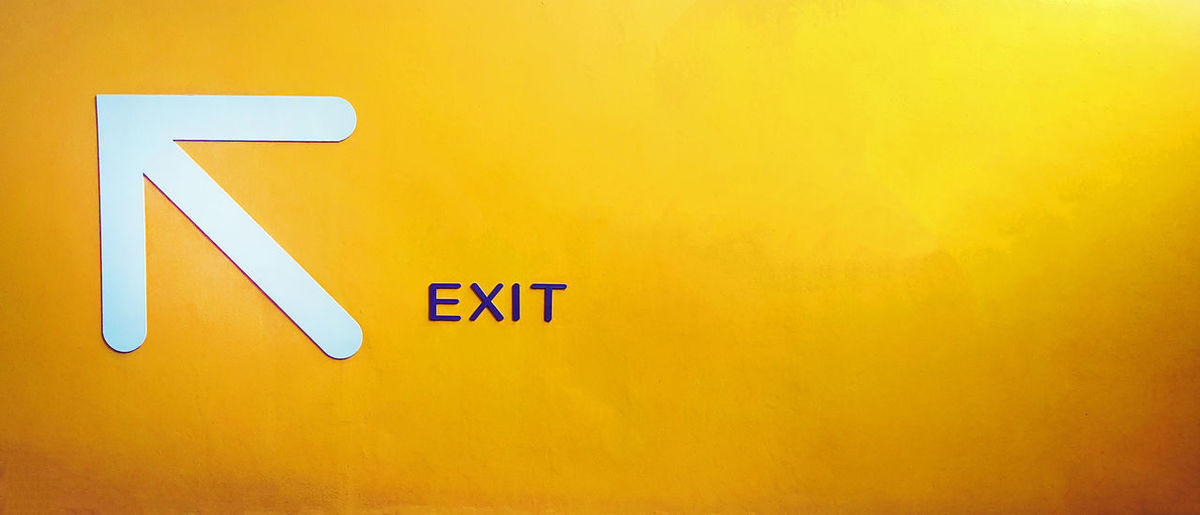 Close-up of road sign on yellow wall