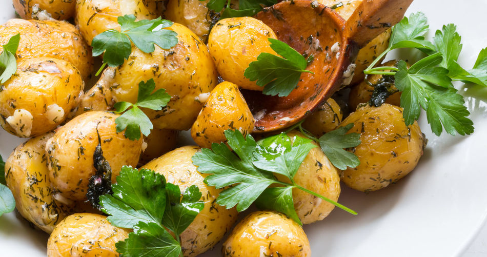 High angle view of prepared potatoes with cilantro in plate