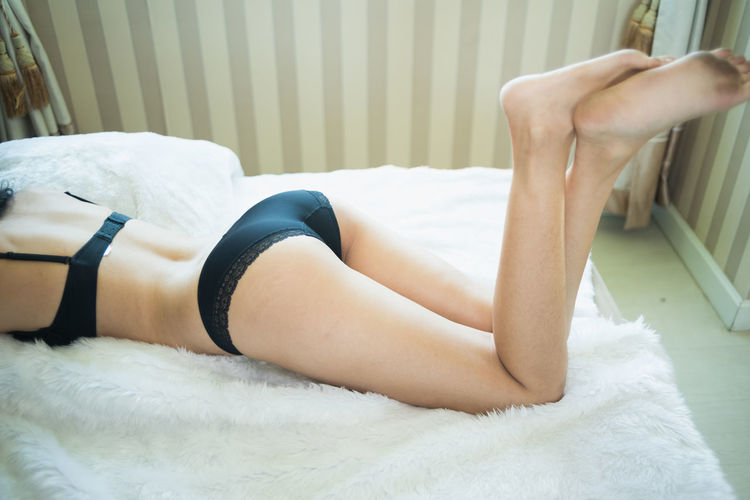 Low section of woman lying on bed at home