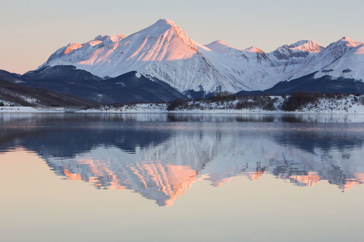 Snowcapped mountains reflecting on lake