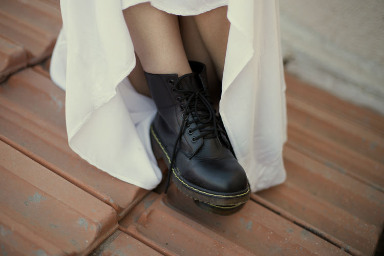 Portrait of woman's shoes wearing a white dress sitting ok the roof