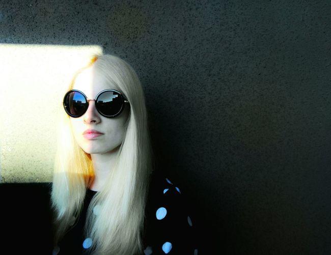 Sunlight Falling On Beautiful Woman Wearing Sunglasses Against Wall