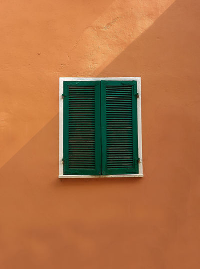 Closed window on brown wall