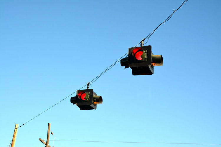 Low Angle View Of Stoplights Against Clear Blue Sky