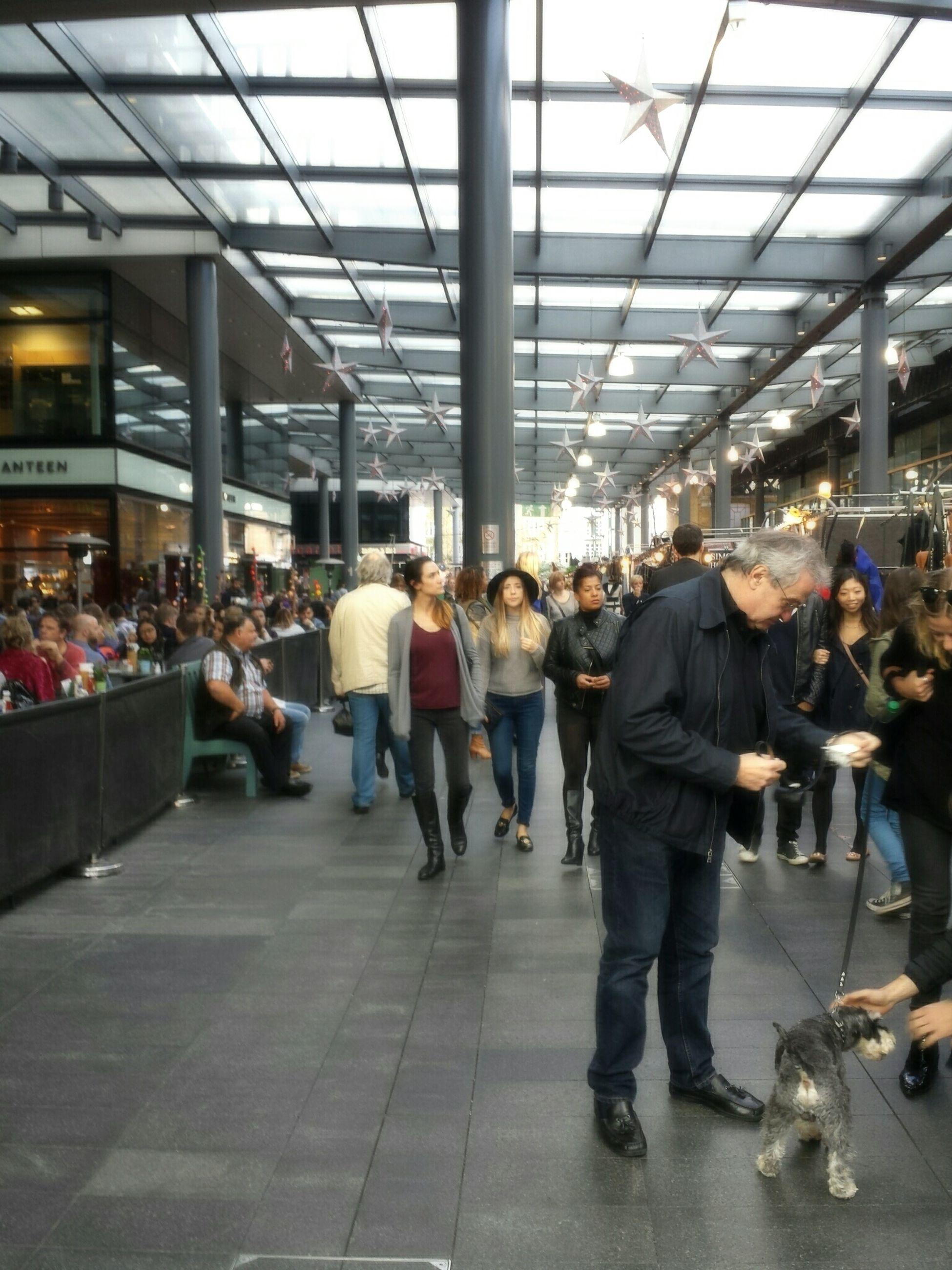 indoors, large group of people, men, person, retail, lifestyles, market, market stall, shopping, store, for sale, leisure activity, city life, consumerism, walking, choice, illuminated, standing, ceiling