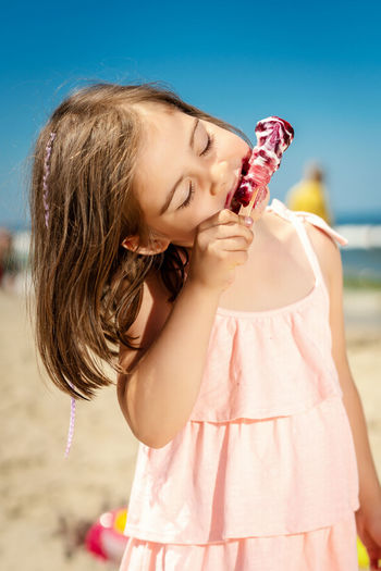 Cute girl with eyes closed eating ice cream at beach