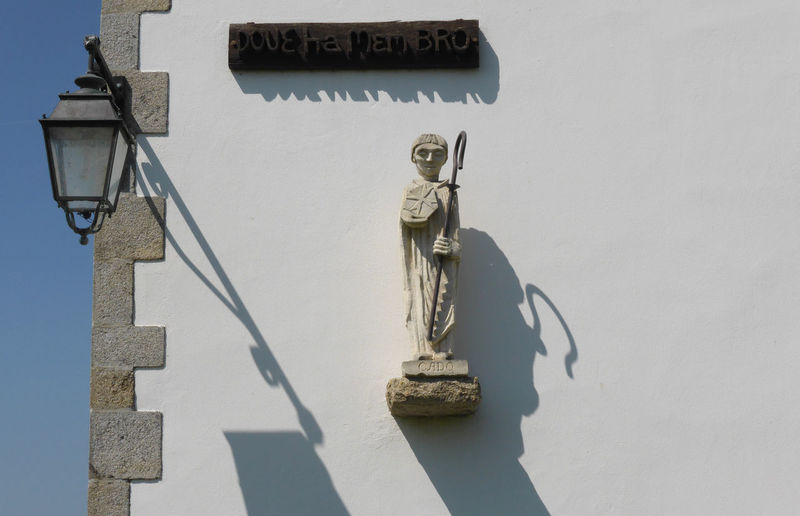 Statue mounted on white wall