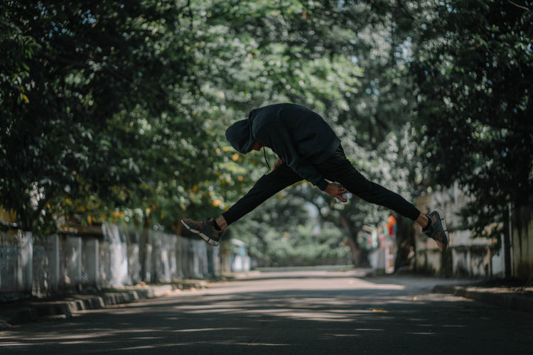 Side View Of Young Man Jumping On Road Against Trees
