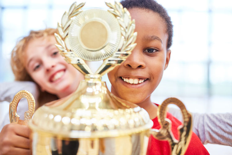 Close-up portrait of boy holding trophy
