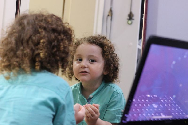 Portrait Of Boy Reflecting In Mirror At Home