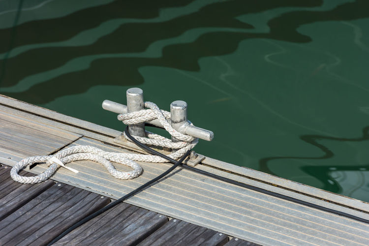 Close-up of rope tied to metal on pier