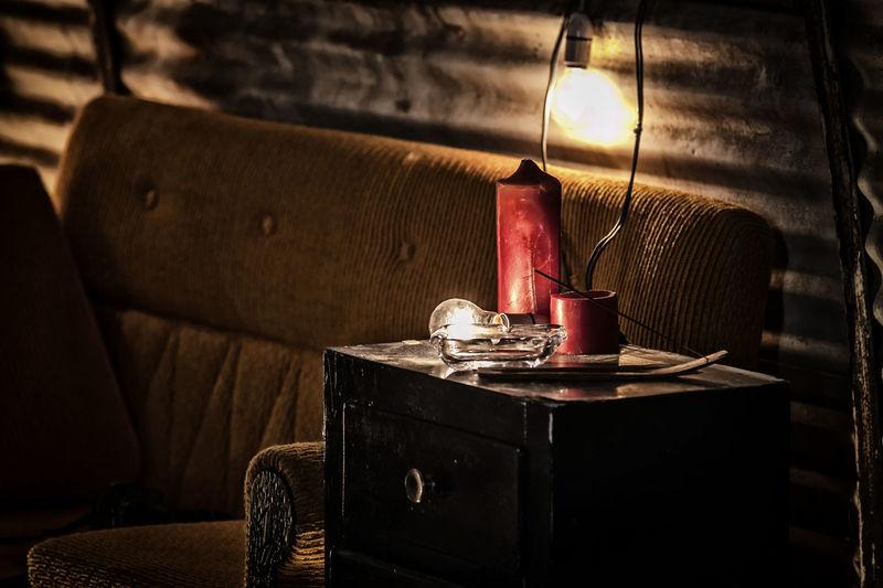 Illuminated light bulb on table by sofa