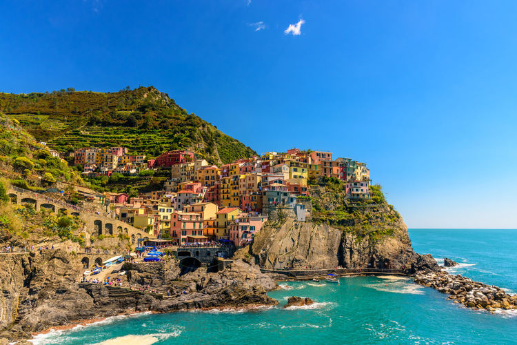 View of the beautiful town of Manarola inside the Cinque Terre National Park in Liguria, Italy Architecture Beach Beauty In Nature Blue Building Building Exterior Built Structure Cinque Terre Clear Sky Cliff Day Horizon Over Water Liguria Manarola Mountain National Park Nature No People Outdoors Rock - Object Scenics Sea Sky Sunlight Water