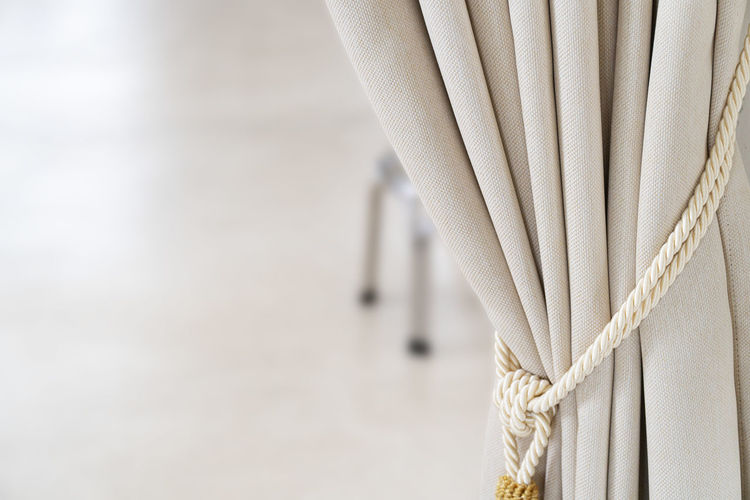 Close-up of rope tied on curtain at home