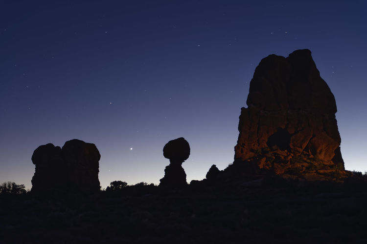 Silhouette rock formations against sky at night