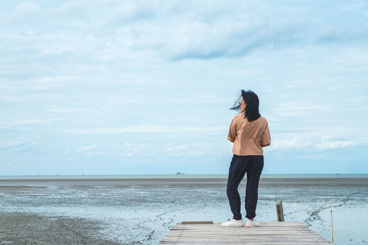 Woman standing on pier over sea against sky