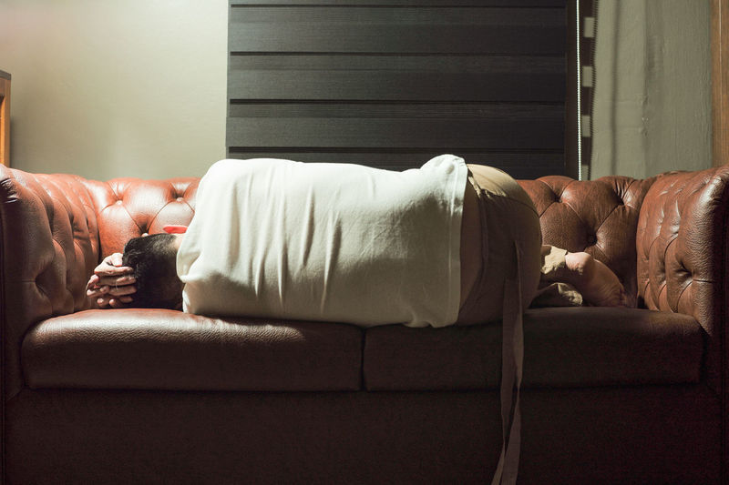 Rear view of man sleeping on sofa at home