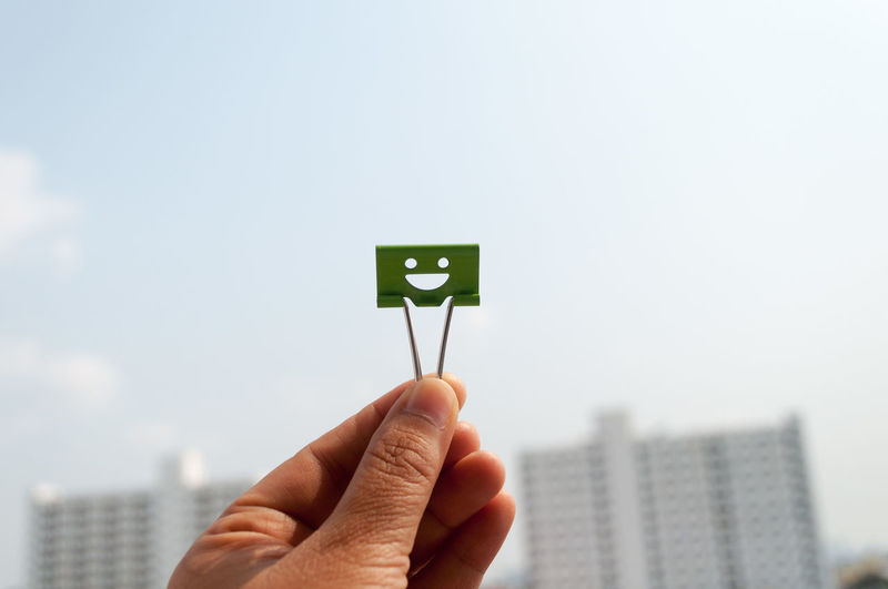 Cropped hand holding green anthropomorphic smiley face on paper clip against sky