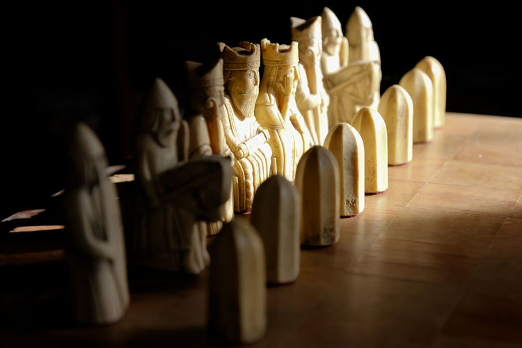 Chess set Lewis Chessman Bishop - Chess Piece Black Background Board Game Carved Chess Chess Board Close-up History In A Row Indoors  King - Chess Piece Knight - Chess Piece Large Group Of Objects No People Pawn - Chess Piece Queen - Chess Piece Rook - Chess Piece Selective Focus Side By Side Still Life Table The Past Wood Wood - Material
