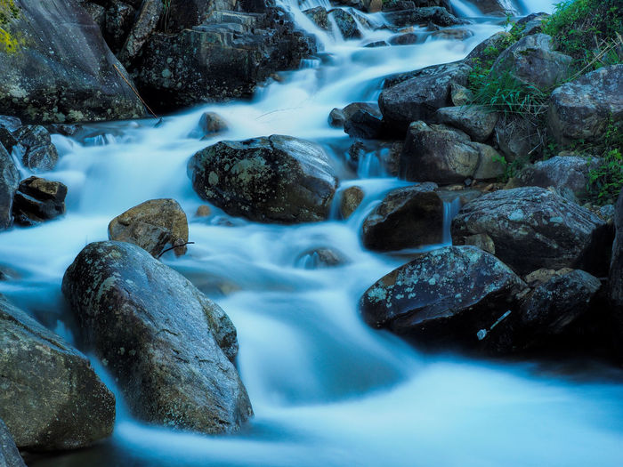 Blurred motion of stream flowing amidst rocks in forest