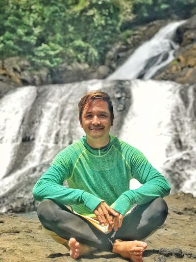 Portrait of smiling man sitting on rock