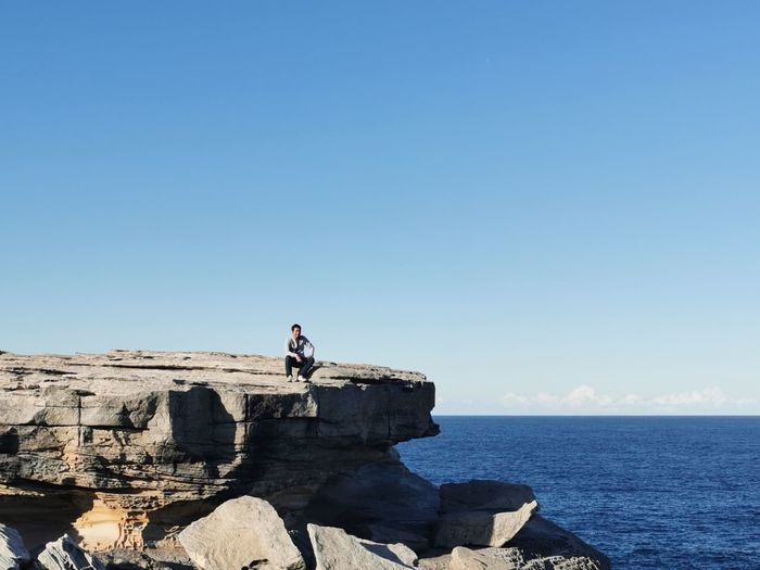 Man sitting on rock formation by sea against blue sky