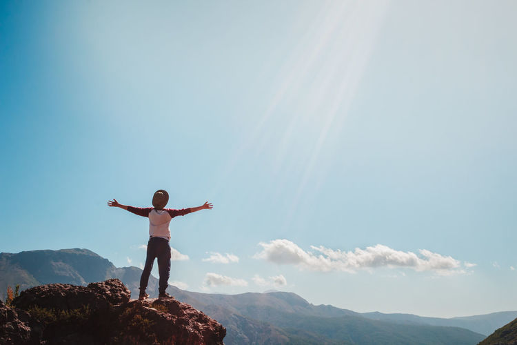 Arms Outstretched Beauty In Nature Day Energetic Full Length Leisure Activity Lifestyles Mountain Mountain Range Nature One Person Outdoors People Real People Rear View Scenics Sky Standing Young Adult