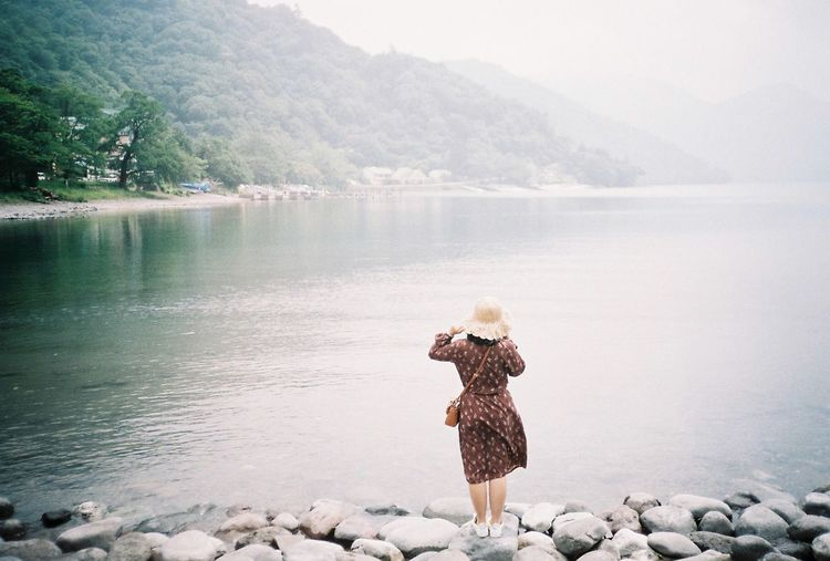 Rear view of woman standing on rocks by lake