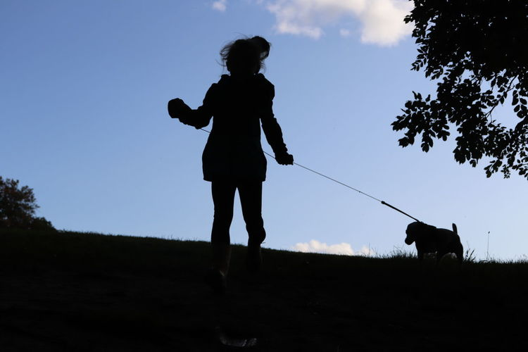 Silhouette man with dog on field against sky