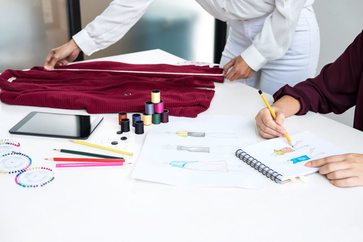 Midsection of fashion designers working while taking measurement of textile on table in office
