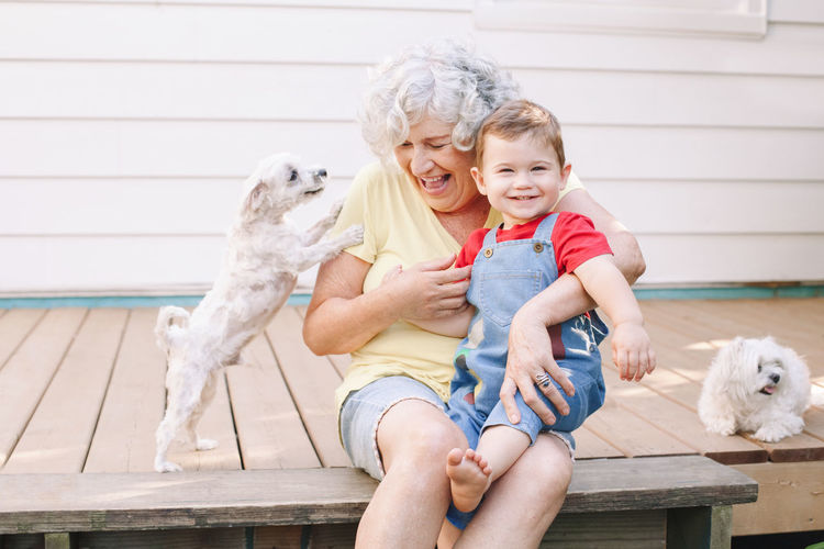 Senior woman and boy with dogs sitting outdoors
