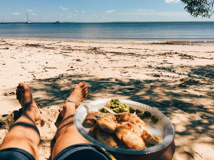 Low section of man holding food plate while relaxing at beach