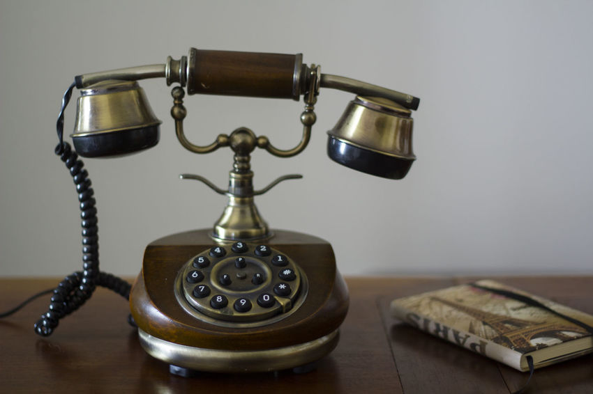 Vintage phone on wooden table and closed phonebook on the side Antiquated Antique Classic Retro Analog Antique Call Communication Connection Dial Handset Landline Phone No People Nostalgia Number Old Old Telephone Phone Retro Styled Style Table Technology Telecommunications Equipment Telephone Vintage
